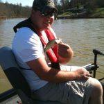 small bass tracker aluminum bass fishing boat wearing inflatable life jacket