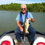 Freddie showing off his largemouth bass on his new Tracker aluminum bass fishing boat from Stokley's Marine wearing inflatable life jacket