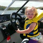 little girl at the helm wheel of yamaha jet boat wearing life jacket